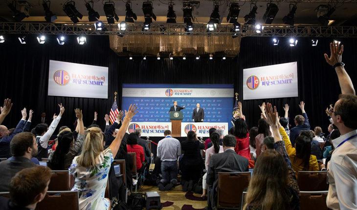 Periodistas levantan la mano en una sala de prensa en Hanói con Donald Trump en segundo plano.